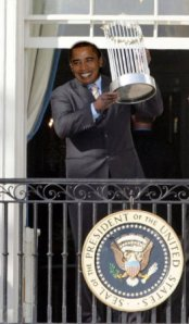 Obama hoists the World Series Trophy sent to him by MLB.